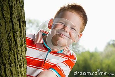 Menino que esconde atrás da árvore