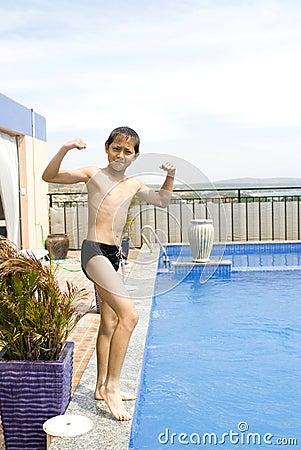 Menino que mostra seu músculo além da piscina