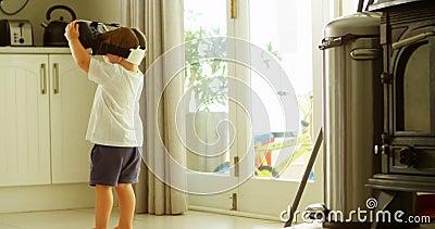 Menino que usa auriculares da realidade virtual na cozinha 4k vídeos de arquivo