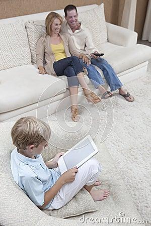 Menino que usa a tabuleta de Digitas com os pais que olham a tevê