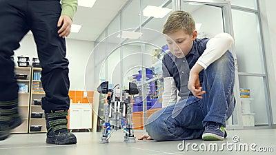 Meninos de escola que fazem robôs feitos a si próprio do elefante no laboratório da escola de engenharia filme