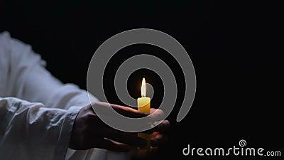 Mens in de witte brandende kaars van de robeholding tegen donkere achtergrond, godsdienstige cultus stock video