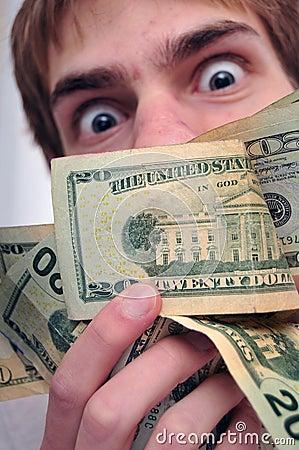 Mens die bij een pakje van contant geld staart