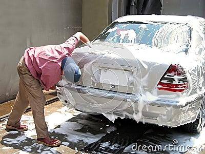 Mens die de auto schoonmaakt