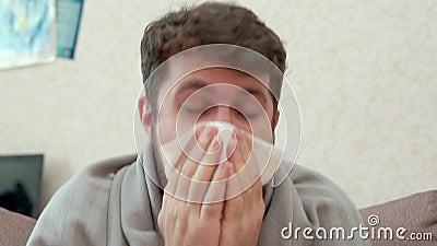 Mens die in een document zakdoek hoesten Hij heeft een koude, hoofdpijn, koorts, kou stock footage