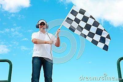 Mens die een geruite vlag op een toevoerkanaal golft