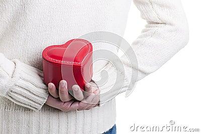 Mens die een hart gevormde doos verbergt
