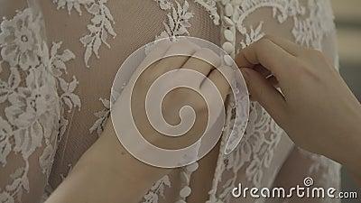Mens die een korset op de kleding van het bruid` s huwelijk binden stock footage