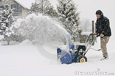 Mens die een krachtige sneeuwblazer met behulp van