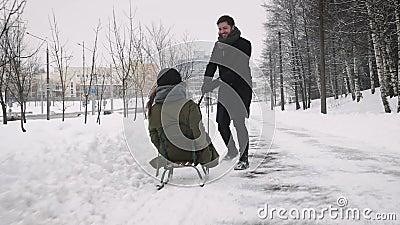Mens die meisje op een slee trekken bij sneeuw stock videobeelden