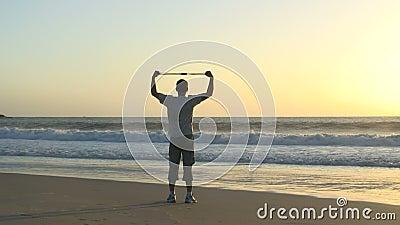 Mens die oefeningen op een strand doen stock video