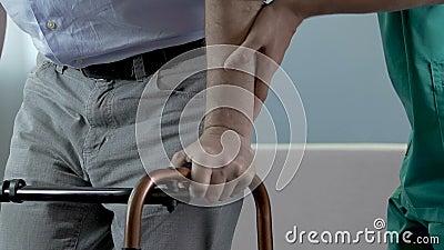 Mens die stappen proberen te maken terwijl het houden op leurder, verpleegster ondersteunend hem door wapen stock footage