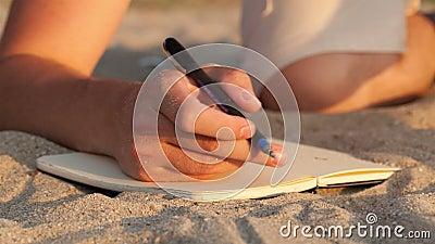 Mens die in zijn agenda bij het strand schrijven