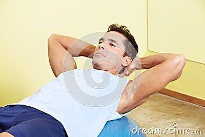 Mens die zitten-UPS in gymnastiek doet