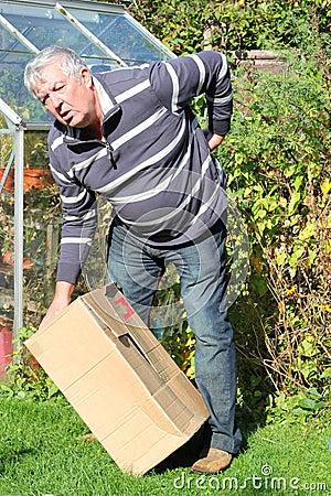 Mens die zware doos opheft en rugpijn krijgt.