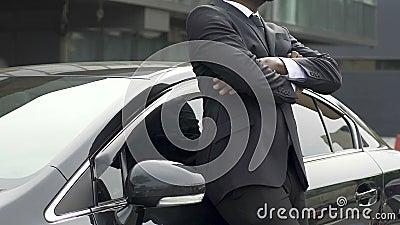 Mens in duur pak die nieuwe auto, gelukkig met aankoop van auto afvegen stock footage