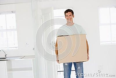Mens met doos die zich in het nieuwe huis glimlachen beweegt