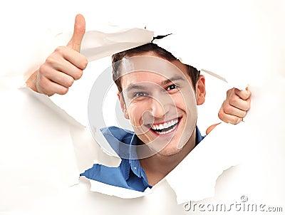 Mens met duimen die omhoog door document gat piepen