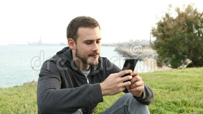 Mensagens de adolescentes sérias ao telefone sentados na grama vídeos de arquivo