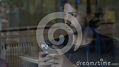 Mensagens de datilografia do menino em seu smartphone que senta-se em amigos de espera sozinhos de um bar para vir video estoque
