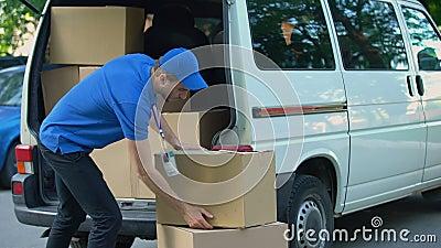 Mensajero que toma las cajas hacia fuera de la furgoneta de entrega, compañía móvil, envío de las mercancías metrajes