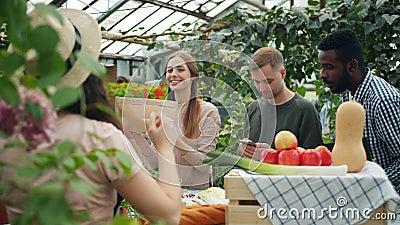 Menschen mit mehreren ethnischen Gruppen, die Bio-Lebensmittel auf dem Agrarmarkt kaufen, nehmen Papiertüten stock video