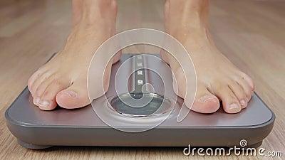 Menselijke voet die bij de weging van schaal voor de controle stappen van de lichaamsmassa terwijl het verliezen van gewicht stock video