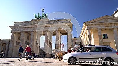 Mensen, fietsers, toeristen, paarden en vervoer overdag door The Brandenburg Gate, Pariser Platz, Berlijn, Duitsland stock videobeelden