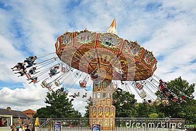Mensen op carrousel onder blauwe hemel met wolken Redactionele Afbeelding