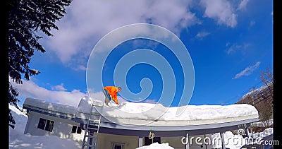 Mensen schoonmakende sneeuw van huisdak 4k stock videobeelden