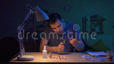 Mensenverslaafde in een donkere ruimte bij een lijst die voor injectie voorbereidingen treffen stock footage