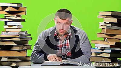 Mensenzitting bij lijst met boeken en lezing een interessant hoofdstuk Het groene scherm stock videobeelden