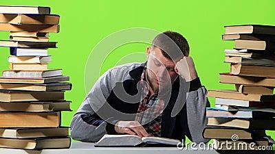 Mensenzitting bij zijn bureau die een handboek doorbladeren Het groene scherm stock videobeelden