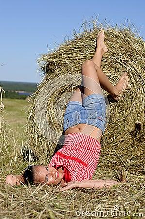 Mentira de la mujer cerca del haystack