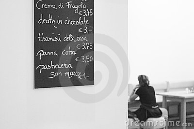 Menu in a cafe on the wall with women sitting on a