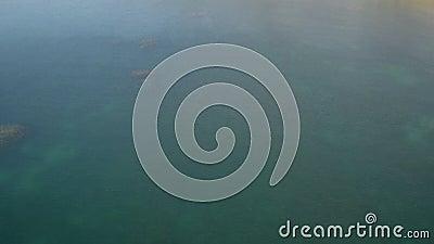Mer de surface azurée lisse avec petite onde. Des blocs solitaires s'élèvent de l'eau clips vidéos