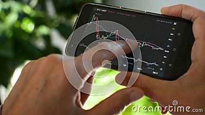 Mercado de Bitmoney, negociação criptográfica em linha, comerciante que trabalha com um telefone celular na bolsa de criptomoeda  vídeos de arquivo