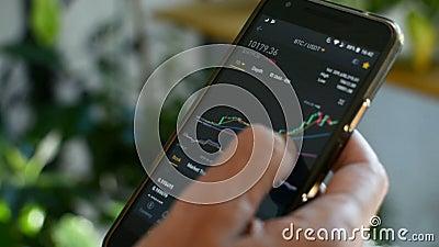 Mercado de Bitmoney, negociação criptográfica em linha, comerciante que trabalha com um telefone celular na bolsa de criptomoeda  video estoque
