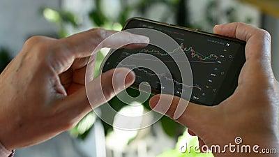 Mercado de Bitmoney, negociação criptográfica em linha, comerciante que trabalha com um telefone celular na bolsa de criptomoeda  filme