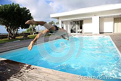 Mergulho do homem na piscina