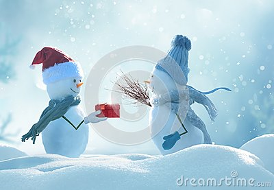 Two cheerful snowmen standing in winter christmas landscape. Stock Photo