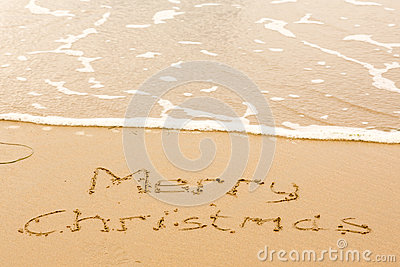 Merry Christmas written in sand on beach