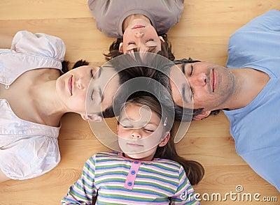 Merry family sleeping lying on the floor