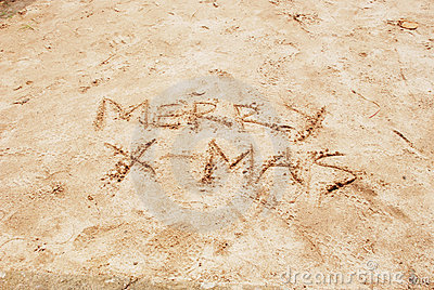Merry X-mas written on beach sand