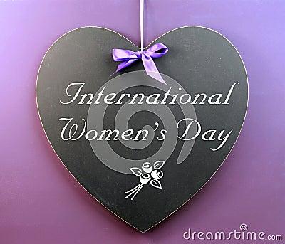 Message du jour des femmes internationales écrit sur le tableau noir de forme de coeur