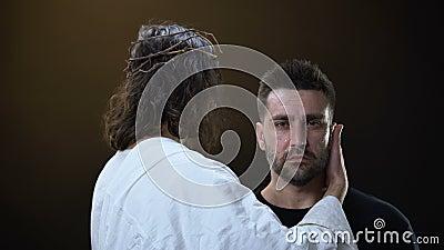 Messie en tissu blanc étreignant le mâle désespéré pleurant, appui religieux, foi banque de vidéos