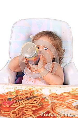 Messy baby girl drinking juice  eating spaghetti