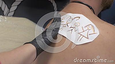 Mestre de tatuagem transfere um esboço de uma tatuagem 'homenzinho' no ombro de um homem desenho infantil de pequenos homens víde video estoque