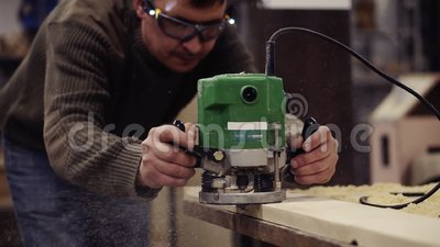 Mestre em óculos protetores trabalhando com máquina de moagem manual em oficina de madeira Moinho de madeira Poeira filme