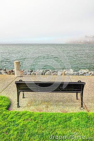 Metal bench on walkway near bay